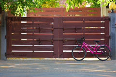 Una bicicletta rosa con il portone di legno su fondo Fotografia Stock