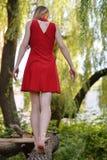 Una bionda in un vestito rosso sta camminando nel parco fotografie stock