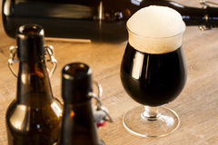 Una birra marrone di vetro, sulla tavola Fotografia Stock Libera da Diritti