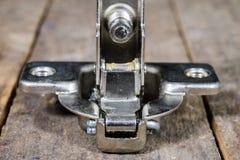 Una bisagra de la artesanía en madera en una tabla de madera del taller Accesorios de la carpintería Foto de archivo libre de regalías