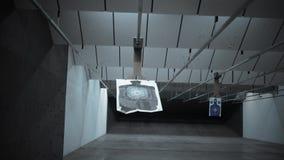 Una blanco de la silueta en una gama del arma resbala lejos de la cámara - versión cinemática oscura almacen de video