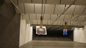 Una blanco de la silueta en una gama del arma resbala lejos de la cámara - versión cinemática oscura metrajes
