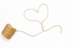 Una bobina della corda e un cappio sotto forma di un cuore su un fondo bianco Fotografie Stock Libere da Diritti