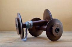Una bobina della ruota di filatura con un capo di filato allegato e una bobina vuota contro un fondo della carta marrone Fotografia Stock Libera da Diritti