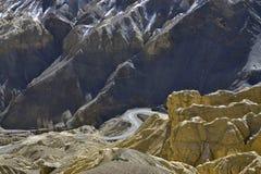Una bobina, bobina della strada asfaltata attraverso le rocce, nella priorità alta là è rocce gialle, nei precedenti di una crest Fotografia Stock
