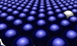 Una bola blanca adentro entre muchas bolas azules Foto de archivo