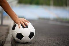 Una bola clásica del fútbol en un fondo asfaltado de la trayectoria Niños que entrenan a fútbol Forma de vida sana Una bola en un Fotos de archivo libres de regalías
