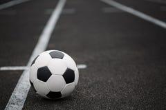 Una bola clásica del fútbol en un fondo asfaltado de la trayectoria Niños que entrenan a fútbol Forma de vida sana Una bola en un Foto de archivo libre de regalías