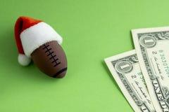 Una bola del rugbi del recuerdo o del fútbol americano en un sombrero rojo de Santa Claus al lado de dos dólares en un fondo verd foto de archivo libre de regalías