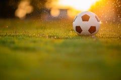 Una bola en el campo de hierba verde para el partido de fútbol del fútbol debajo de la luz y de la lluvia del rayo de la puesta d foto de archivo libre de regalías