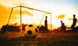 Una bola en el campo de hierba verde para el partido de fútbol del fútbol debajo de la luz y de la lluvia del rayo de la puesta d imagenes de archivo