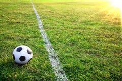 Una bola o un balompié de fútbol en estadio con puesta del sol Imagen de archivo libre de regalías