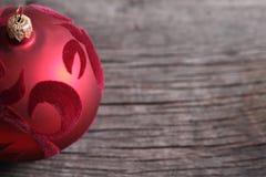 Una bola roja de la Navidad en el fondo de madera Foto de archivo