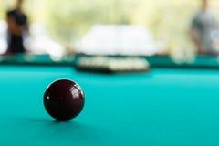 Una bola rojo oscuro en el mantel contra la perspectiva de una pirámide borrosa Imágenes de archivo libres de regalías