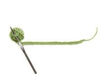 Una bola verde del hilado con un ganchillo Foto de archivo