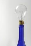 Una bombilla clara en la botella de petróleo azul Fotografía de archivo libre de regalías