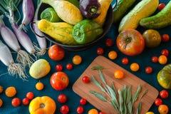 Una bontà di prodotti freschi compreso le cipolle, il pomodoro, la zucca, il pepe, la salvia ed il cetriolo su un fondo colorato  immagine stock