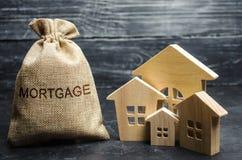 Una borsa con soldi e l'ipoteca di parola e case di legno L'accumulazione di soldi per pagare i tassi di interesse sulle ipoteche fotografie stock