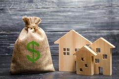 Una borsa con soldi e tre case Concetto di acquisizione e dell'investimento del bene immobile Prestito economico accessibile, ipo immagini stock libere da diritti