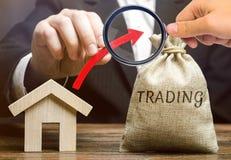 Una borsa dei soldi con il commercio di parola, una freccia alta e una casa di legno Il concetto di aumento della richiesta per l fotografia stock