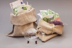 Una borsa di due soldi con l'euro e porcellino salvadanaio di vetro Fotografia Stock Libera da Diritti