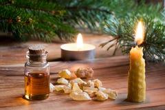 Una botella de aceite esencial del incienso, la Navidad diseñada Foto de archivo
