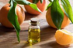 Una botella de aceite esencial de la mandarina en un fondo de madera fotografía de archivo