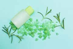 Una botella de aceite esencial y de sal con romero fresco de la hierba en un fondo azul imagen de archivo libre de regalías