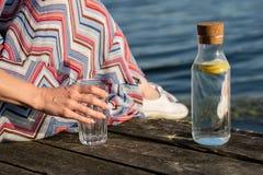 Una botella de agua con el limón y un vidrio Tienda un puente sobre sobre el lago a Fotos de archivo