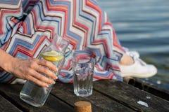 Una botella de agua con el limón y un vidrio Tienda un puente sobre sobre el lago a Fotografía de archivo