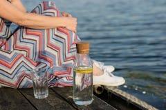 Una botella de agua con el limón y un vidrio Tienda un puente sobre sobre el lago a Fotos de archivo libres de regalías