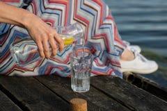 Una botella de agua con el limón y un vidrio Tienda un puente sobre sobre el lago a Imágenes de archivo libres de regalías