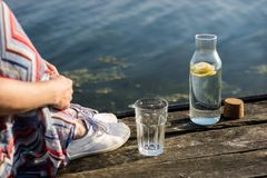 Una botella de agua con el limón y un vidrio Tienda un puente sobre sobre el lago a Foto de archivo