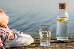 Una botella de agua con el limón y un vidrio Tienda un puente sobre sobre el lago a Imagen de archivo