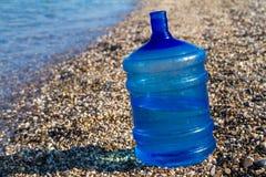Una botella de agua grande se coloca en la playa, fotos de archivo