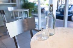 Una botella de agua y de un vidrio en la tabla fotos de archivo libres de regalías