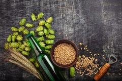 Una botella de cerveza con los saltos, la avena, las espiguillas del trigo y el abrelatas verdes en el tablero de tiza rasguñado  fotos de archivo
