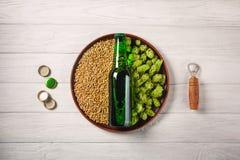 Una botella de cerveza en una placa con los saltos verdes y grano de avena con el abrelatas y de corcks en un tablero de madera b foto de archivo libre de regalías