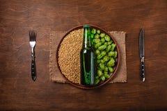 Una botella de cerveza en un grano fresco verde del salto y del trigo con el cuchillo y de bifurcación en una placa contra el tab fotografía de archivo libre de regalías