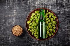 Una botella de cerveza en un salto fresco verde en una placa con el grano de avena contra la perspectiva de una pizarra rasguñada imagenes de archivo