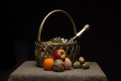 Una botella de champán en una cesta de la paja con la malla a del ` s del Año Nuevo Foto de archivo