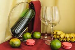 Una botella de copas de vino y de fruta Foto de archivo