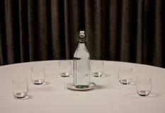 Una botella de cristal de agua con un platillo y los vidrios colocados en una tabla cubierta por el mantel blanco En el fondo una imagen de archivo