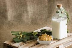Una botella de cristal con leche fresca y una decoración floral imágenes de archivo libres de regalías