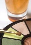 Una botella de la paleta y de perfume del maquillaje Foto de archivo