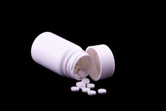 Una botella de píldora blanca con las píldoras blancas en un fondo negro Imagenes de archivo
