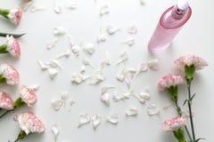 Una botella de perfume rosada con el clavel rosado y blanco florece foto de archivo libre de regalías