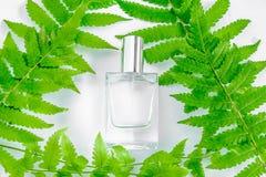 Una botella de perfume y de flores blancos con las hojas imagenes de archivo