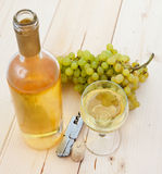 Una botella de vino blanco, de uvas y de una copa Foto de archivo libre de regalías