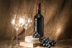 Una botella de vino con dos vidrios vacíos fotografía de archivo libre de regalías